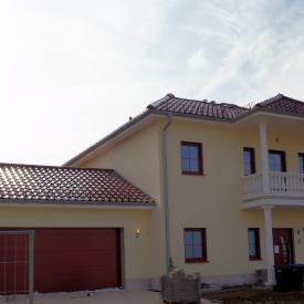 Neubau mit roten Schüco Fenstern, Inotherm Haustüre und roten Garagentor.